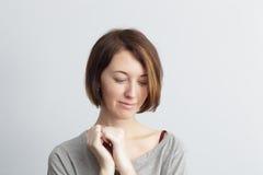 A menina tímida e bonita olha para baixo bashfully, embreando algo Imagens de Stock Royalty Free
