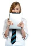 Menina tímida que esconde sua face com um dispositivo da tabuleta Imagem de Stock