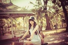 A menina tailandesa asiática bonito na roupa do vintage está montando uma bicicleta, no parque ensolarado do verão Imagens de Stock