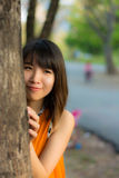 Menina tailandesa bonito que esconde atrás da árvore Imagens de Stock Royalty Free