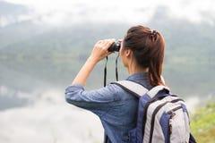 Menina tailandesa da aventura que wathcing com binóculos imagens de stock royalty free