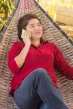 A menina tailandesa feliz está falando no telefone celular a uma comunicação com foto de stock