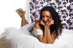 Menina Tanned na cama - dirija nas mãos Imagem de Stock