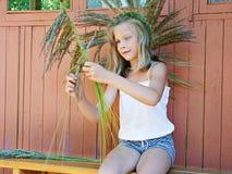 A menina tece uma grinalda da grama Fotos de Stock