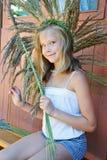 A menina tece uma grinalda da grama Fotografia de Stock Royalty Free