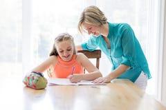 Menina teenaged de ajuda da mãe com trabalhos de casa imagens de stock