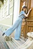 A menina Teenaged no vestido do fato-macaco est? batendo na porta do vintage imagem de stock