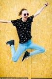 Menina teenaged nova que salta na frente da cerca do pa de madeira do mdf fotos de stock