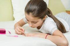 A menina tem 10 anos velha em casa na cama em sua roupa home, prega seus pregos usando acessórios do tratamento de mãos Imagens de Stock Royalty Free