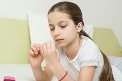 A menina tem 10 anos velha em casa na cama em sua roupa home, prega seus pregos usando acessórios do tratamento de mãos Fotos de Stock Royalty Free