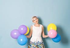 A menina tem o divertimento com os balões coloridos no fundo azul Imagem de Stock Royalty Free