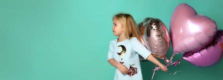 A menina tem o divertimento com um grupo de balões de ar cor-de-rosa na forma de seu coração imagens de stock royalty free