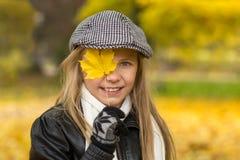A menina tem o divertimento que joga com a folha amarela no parque do outono Fotos de Stock Royalty Free