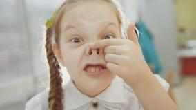 A menina tem o nariz leitão engraçado, do sorriso e das mostras Fotos de Stock
