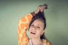 A menina tem problemas do cabelo Mulher adolescente que tem o problema com cabelo desalinhado tangled Conceito dos problemas de H fotografia de stock