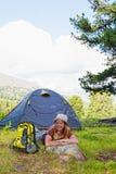 A menina tem um descanso na barraca verde fotografia de stock royalty free