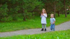 A menina tem uma maçã no parque com seu irmão mais novo video estoque