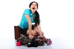 A menina tenta coloc a roupa em uma mala de viagem velha fotos de stock royalty free