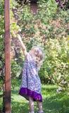 A menina tenta manter a etapa com flores imagens de stock royalty free