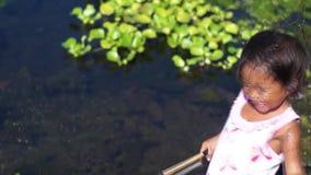 A menina tenta pescar como batidas das ervas daninhas em sua cara filme