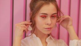 A menina tenta sobre brincos na parede cor-de-rosa video estoque