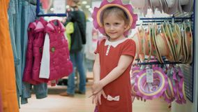 A menina tenta sobre um chapéu e ensaca-o em uma loja, tem-no o divertimento e o sorriso Compra dos miúdos filme