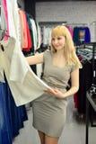 A menina tenta sobre um vestido novo na loja Fotos de Stock