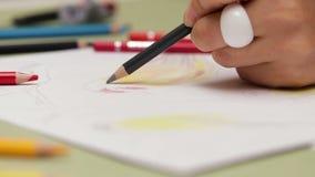A menina tira canhoto com o lápis preto no papel, vista detalhada em slowmotion filme