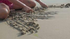 A menina tira figuras na areia nos beachbeaches vídeos de arquivo