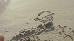 A menina tira figuras na areia nos beachbeaches filme