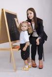 A menina tira na casa da placa, professor ajuda-a Foto de Stock Royalty Free