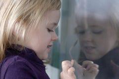 A menina tira na janela Imagens de Stock Royalty Free