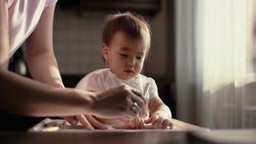 A menina tira no papel A mamã vem e começa ajudar sua filha a pintar vídeos de arquivo