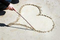 a menina tira um coração com uma vara na areia imagens de stock
