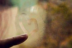 A menina tira um coração no vidro enevoado outono chuvoso dourado no fundo fotos de stock