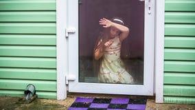 A menina tira um dedo no vidro da porta transparente filme