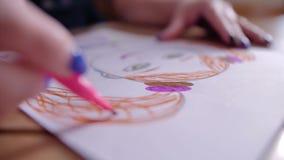 A menina tira um desenho colorido em uma folha branca com uma caneta com ponta de feltro Folha e marcadores do close-up Vista bon video estoque