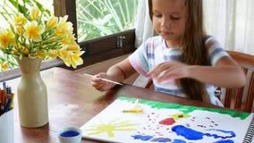 A menina tira uma paleta de pinturas da aquarela O processo de criar uma pintura da aquarela video estoque