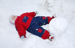 A menina tired pequena encontra-se na neve perto do snowball grande Imagem de Stock Royalty Free