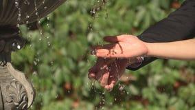A menina toca em um córrego da mão da água da fonte, movimento lento closeup video estoque