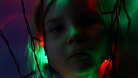 A menina toca na esfera colorida perto das lâmpadas leves da festão na obscuridade video estoque