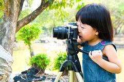 A menina toma a fotografia exterior Fotos de Stock Royalty Free