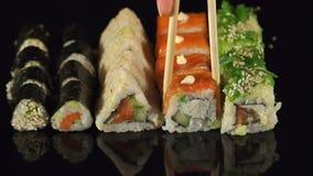 A menina toma hashis de madeira sushi, close-up video estoque