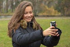 A menina toma imagens com seu telefone celular fotografia de stock