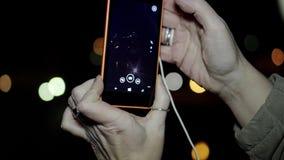 A menina toma imagens na arquitetura da cidade da noite do telefone Close-up das mostras da m?o da menina com o telefone filme