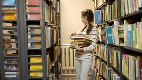 A menina toma livros da biblioteca da prateleira video estoque