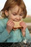 A menina toma a mordida grande do sanduíche Foto de Stock Royalty Free