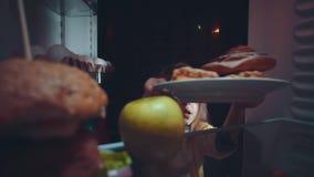 A menina toma o alimento fora do refrigerador na noite filme