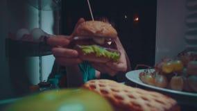 A menina toma o alimento fora do refrigerador na noite video estoque