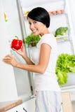 A menina toma a pimenta vermelha do refrigerador aberto Foto de Stock